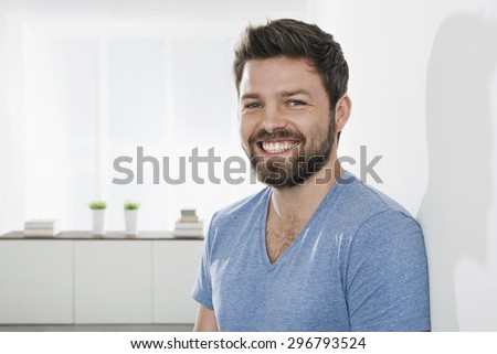 Portrait of young smiling man leaning against wall