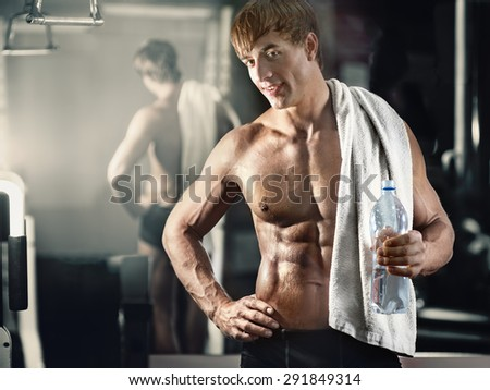 Portrait of young smiling muscular man with towel and bottle of water in gym after fitness workout - stock photo