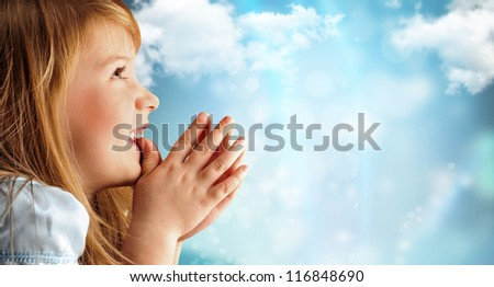 Portrait of young smiling praying girl in blue dress against sky background. Lots of copyspace - stock photo