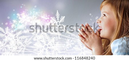 Portrait of young smiling praying girl looking up in blue dress against silver fairy snowstorm background - stock photo
