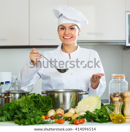 Portrait of young smiling professional chef with vegetables and herbs