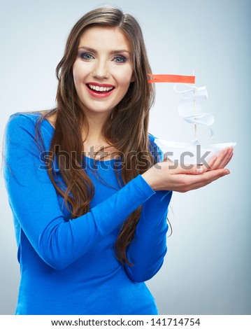 Portrait of young smiling woman blue dressed hold white paper ship. Female model isolated studio portrait. - stock photo