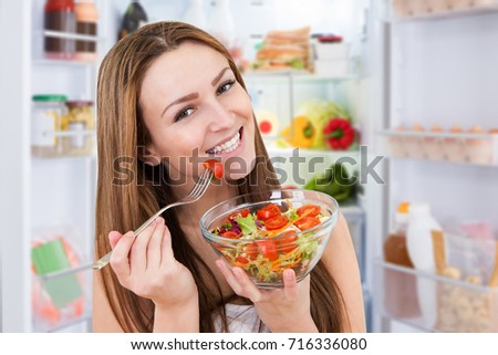 Portrait Of Young Smiling Woman Eating Fresh Healthy Salad