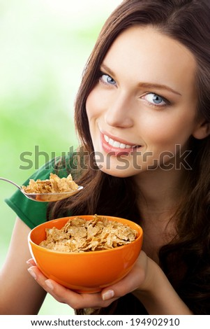Portrait of young smiling woman eating muesli or cornflakes, outdoors - stock photo