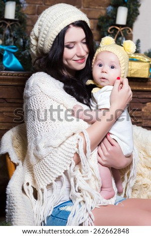 Portrait of young smiling woman holding her baby - stock photo