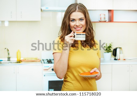 Portrait of young smiling woman holds a cup with coffee or tea against kitchen background. Yellow color clothes. - stock photo