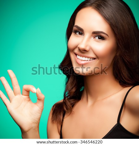 Portrait of young smiling woman in black tank top clothing, showing okay gesture, with blank copyspace area for text or slogan, on green background - stock photo