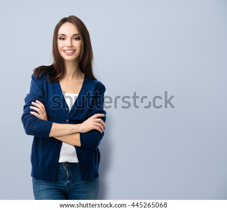 Portrait of young smiling woman in casual smart blue clothing with crossed arms, with copyspace area for text or slogan