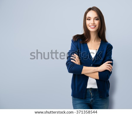 Portrait of young smiling woman in casual smart blue clothing with crossed arms, with copyspace for slogan or text message - stock photo