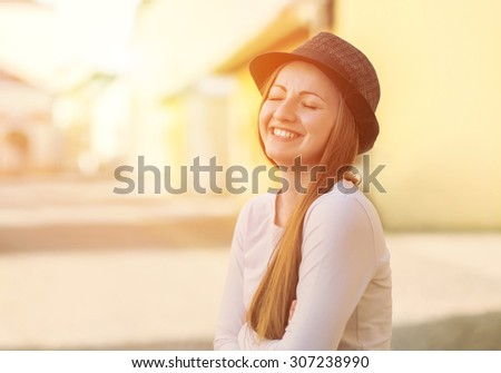 Portrait of young smiling woman in hat on the street - stock photo