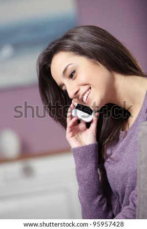 portrait of young smiling woman on phone - stock photo