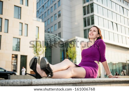 Portrait of young smiling woman on street with buildings in background - stock photo