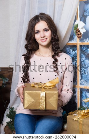 Portrait of young smiling woman posing with a golden gift box - stock photo