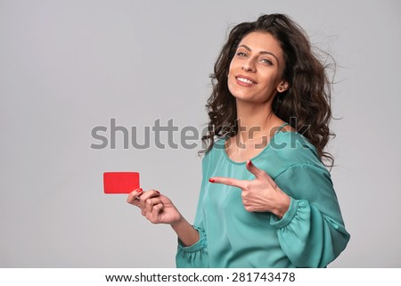 Portrait of young smiling woman showing blank credit card and pointing at it,  isolated on gray background - stock photo