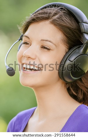Portrait of young smiling woman wearing earphones with microphone standing at summer green park. - stock photo