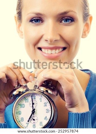 Portrait of young smiling woman with alarmclock - stock photo