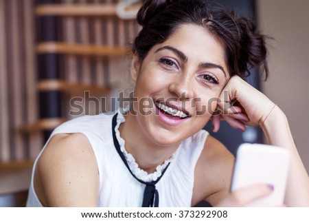 Portrait of young smiling woman with braces  - stock photo