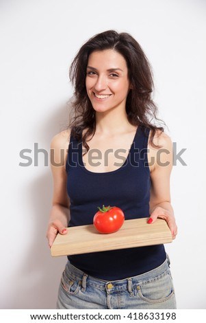 Portrait of young smiling woman with cutting board and tomato. Concept of vegetarian dieting, raw food ingredients, healthy and joyful living