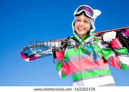 portrait of young smiling woman with snowboard on ski holiday in mountains  - stock photo