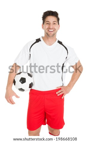 Portrait of young soccer player holding football over white background - stock photo
