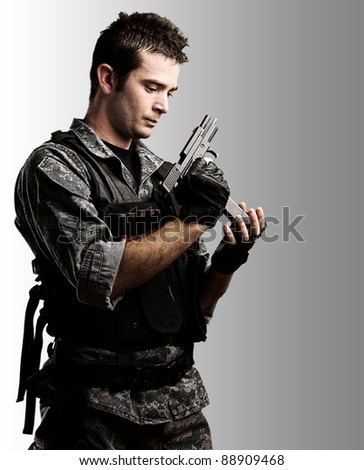 portrait of young soldier aiming with gun against a grunge wall