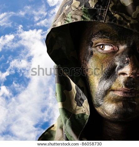 portrait of young soldier face wearing hood against a cloudy sky background - stock photo