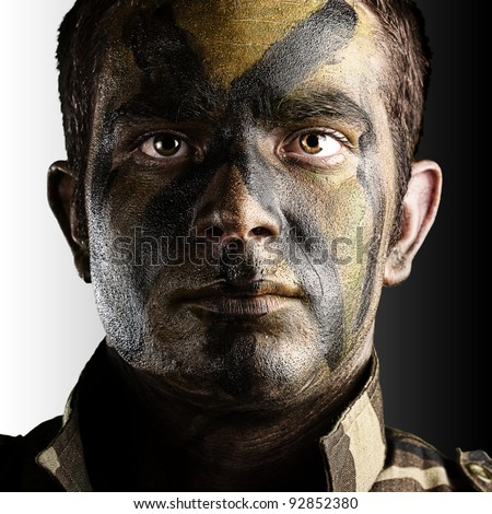 portrait of young soldier face with jungle camouflage paint against a white and black background