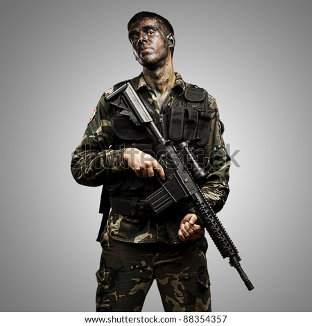 portrait of young soldier painted with jungle camouflage holding riffle over grey background - stock photo