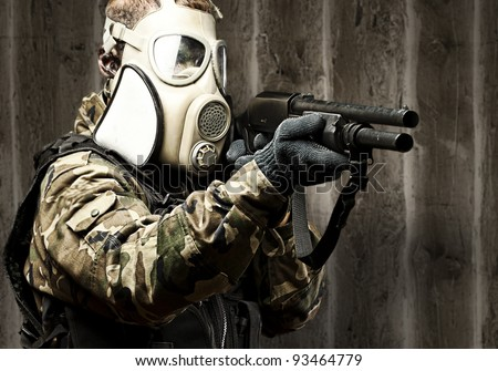 portrait of young soldier with gas mask aiming with shotgun against a grunge wall