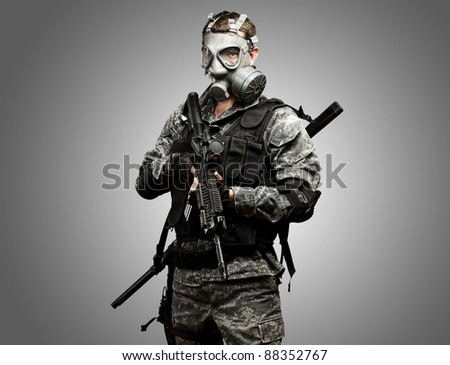 portrait of young soldier with gas mask and rifle against a grey background