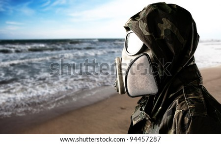 portrait of young soldier with gas mask in the beach - stock photo