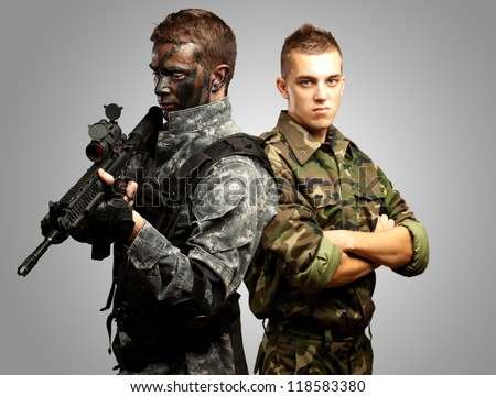 Portrait Of Young Soldier With Jungle Camouflage Paint On A White Background