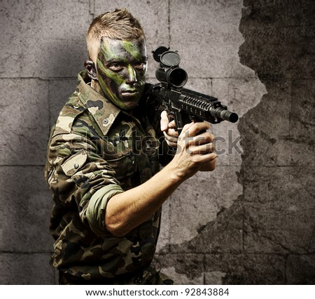 portrait of young soldier with jungle camouflage pointing with rifle against a grunge background - stock photo