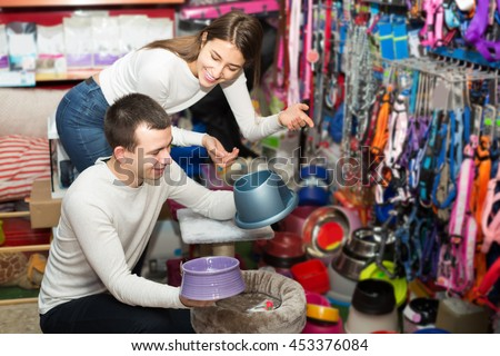 Portrait of young spanish couple purchasing pet bowls in petshop - stock photo