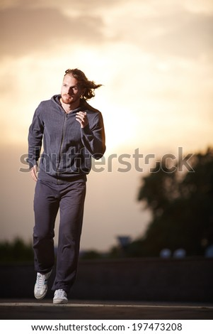 Portrait of young sportsman running in the evening