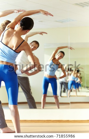Portrait of young sporty girl and guy doing physical exercise - stock photo