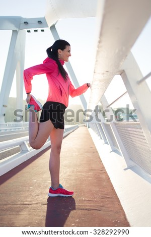 Portrait of young sporty woman dresses in tracksuit stretching muscles of legs before start her daily jog, athletic female doing warm up exercise, sporty girl doing physical training in the fresh air - stock photo