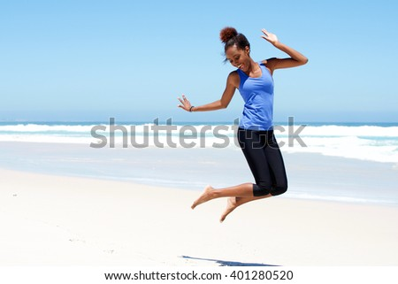 Portrait of young sporty woman jumping with joy at the beach - stock photo