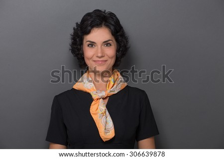 Portrait of young stewardess smiling over grey background. Lady with balck hair ready for her flight. She has a yellow neckcloth. - stock photo