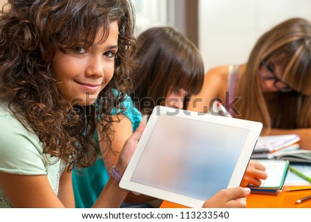 Portrait of young student at desk showing digital tablet with blank copy space.