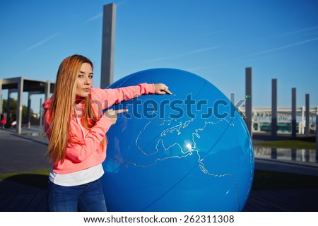 Portrait of young student girl pointing to the earth globe standing on school campus, science art globe object, attractive female teenager standing near big world globe outdoors - stock photo