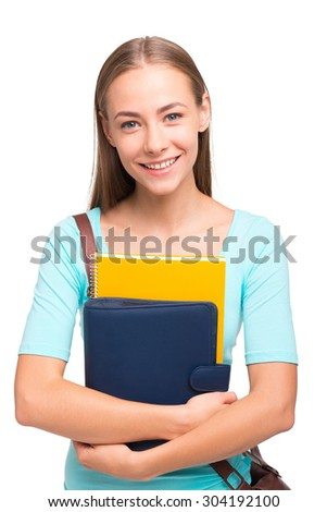 Portrait of young student girl smiling, looking at camera and holding books. Isolated on white background