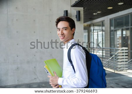 portrait of young student holding book at campus
