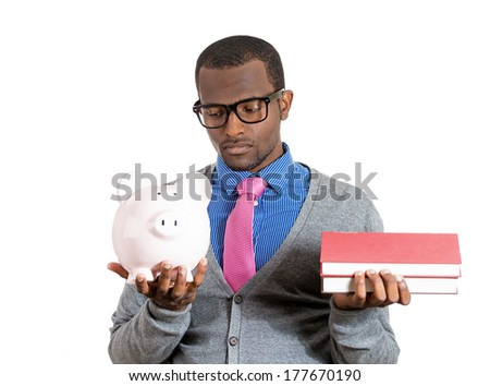 Portrait of young student holding books in one hand, piggy bank in other, looking thoughtful, skeptical, uncertain, questioning dogma, isolated on white background. Value, cost of education concept - stock photo