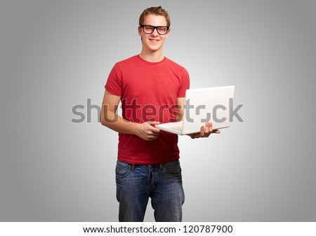 portrait of young student man holding laptop over grey background