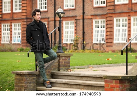 portrait of young student standing against college building - stock photo