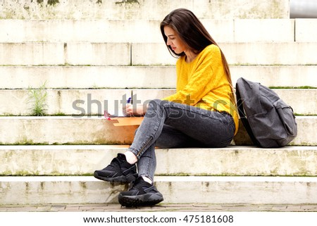 Portrait of young student working on homework on steps