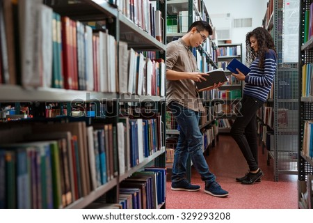 Portrait of young students reading books in library - stock photo