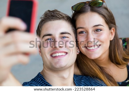 Portrait of young students taking photos with a smartphone in the street. - stock photo