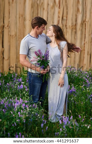 portrait of young stylish fashion couple posing in field